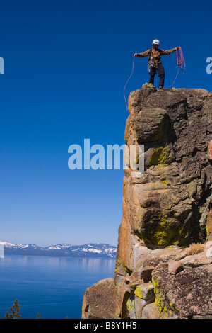 Mountaineer standing on top of a cliff and coiling his climbing rope, Lake Tahoe, Nevada, USA - Stock Photo