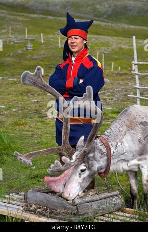 Sami tribal man standing beside a reindeer, Honningsvag, Mageroya Island, Nordkapp, Finnmark County, Norway - Stock Photo