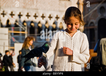 Girl feeding a pigeon in San Marcos Square, Venice, Italy, Europe - Stock Photo