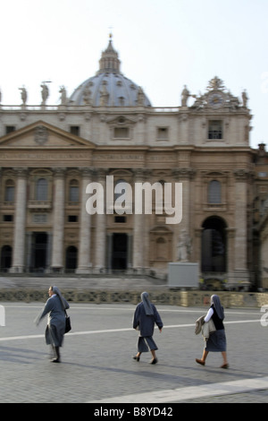 three nuns walking in st peter's square in rome - Stock Photo