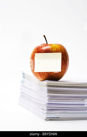 An apple on a stack of paper close-up. - Stock Photo