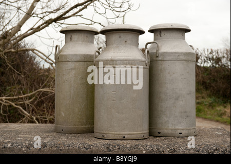 Three old fashioned metal milk churns on a stand on a farm Pembrokeshire Wales UK - Stock Photo