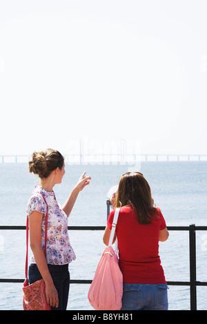 Two women admiring the Oresund bridge Skane Sweden. - Stock Photo