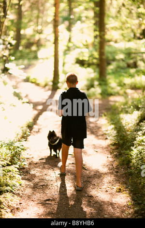 A boy walking a dog in the forest Sweden. - Stock Photo