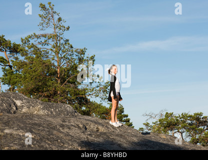 A girl on a cliff Sweden. - Stock Photo