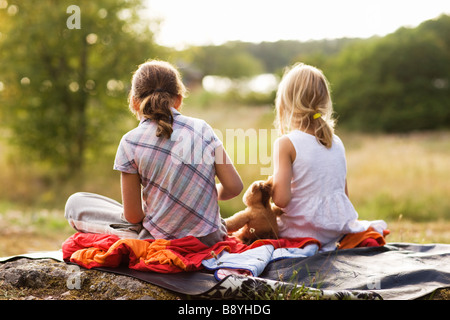 Two girls sitting on a blanket Sweden. - Stock Photo