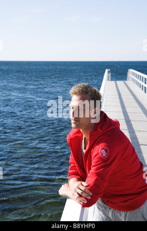 A man standing on a jetty Skane Sweden. - Stock Photo