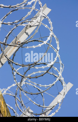 Coils of Razor wire and supports against blue sky - Stock Photo