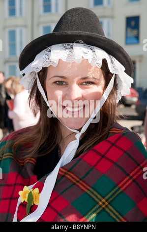 March 1st St David's day a young woman in Welsh National Costume Wales UK - wearing a traditional lace trimmed tall - Stock Photo