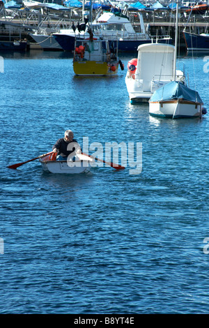 Man rowing out to his boat in the Torquay harbour, Torquay, South Devon - Stock Photo