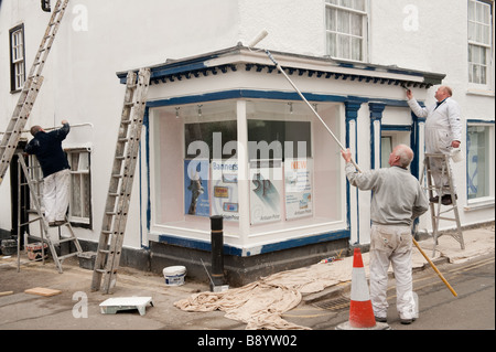 Three painters painting the exterior of a shop in Presteigne village Powys on the welsh english border Wales UK - Stock Photo