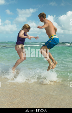Boy and girl jumping over waves - Stock Photo