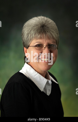 A mature caucasian woman with gray hair wearing glasses and a sweater - Stock Photo