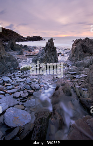 Stream passing between pebbles and rock formations heading towards the sea Combesgate Beach Woolacombe Devon England - Stock Photo
