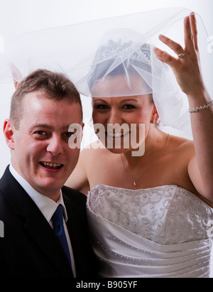 Bride and Groom on wedding day, marriage, bride in white wedding dress, gown with veil and tiara - Stock Photo