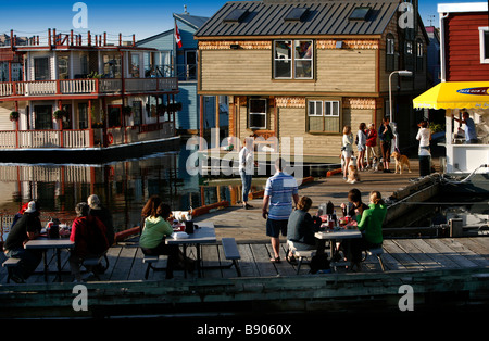 Tourists visit the docks and float homes at Fisherman's Wharf in Victoria, British Columbia, Canada. - Stock Photo