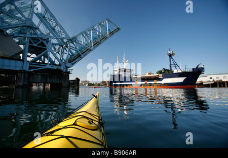 A sea kayaker paddles under the Johnson Street Bridge in Victoria's Inner Harbour on Vancouver Island, British Columbia, - Stock Photo