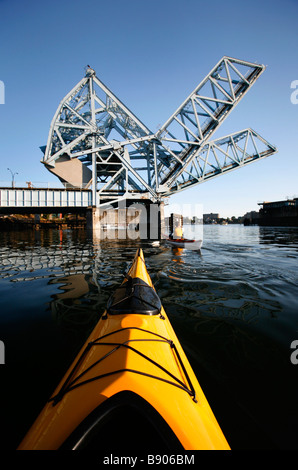 Sea kayakers paddle under the Johnson Street Bridge in Victoria's Inner Harbour on Vancouver Island, British Columbia, - Stock Photo