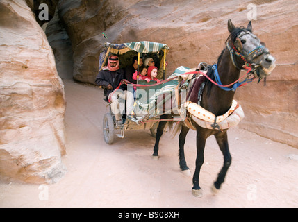 A family of tourists arrive at Petra by horse and cart through the Siq, Petra, Jordan - Stock Photo