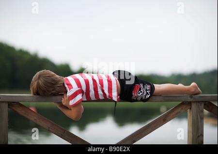 A boy lying on a fence Sweden. - Stock Photo