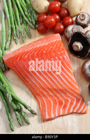 A raw salmon steak on a chopping board with mushrooms asparagus cherry tomatoes and potatoes - Stock Photo