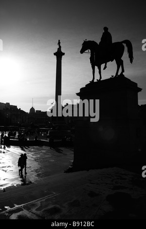 Statue of King George IV and Nelson's Column silhouetted by the low Winter sun, Trafalgar Square, London - Stock Photo