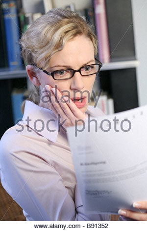 woman reading a letter getting bad news - Stock Photo