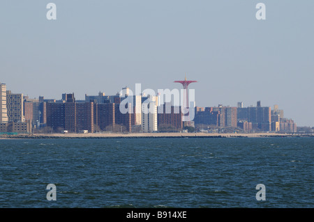 The famed Parachute Jump in Coney Island towers over the apartment buildings that line the beach. - Stock Photo