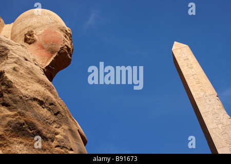 Head of colossal stone carved osiris statue and Obelisk of Queen Hatshepsut against blue sky, Temple of Karnak, - Stock Photo