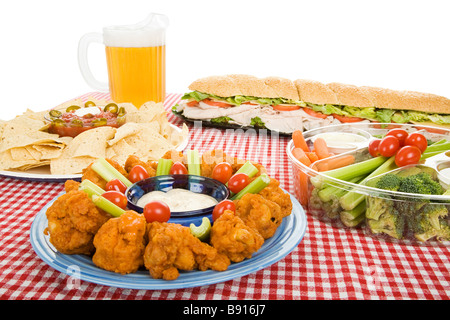Table set with a variety of party foods and a pitcher of beer White background  - Stock Photo