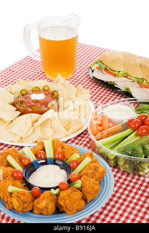 Table set with party snack food platters and a pitcher of beer  - Stock Photo