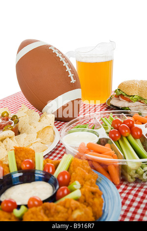 Table set with snack foods for a Super Bowl party focus on football Vertical view with white background  - Stock Photo