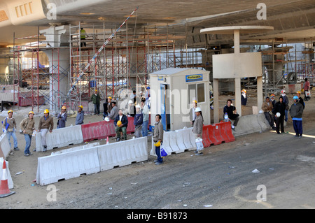 Dubai construction site workers under a new Metro line viaduct waiting for transport - Stock Photo