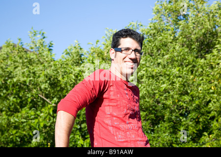 Geeky guy in red - trees behind him - Stock Photo