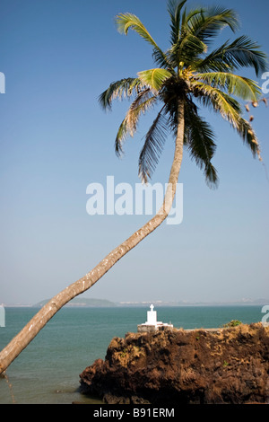 Bended palm over sea with white shrine on background. - Stock Photo