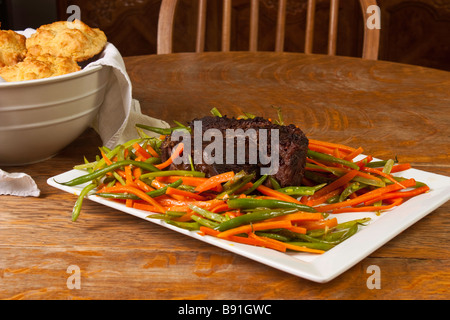 Beef Pot Roast and julienned green beans and carrots  on a white platter - Stock Photo