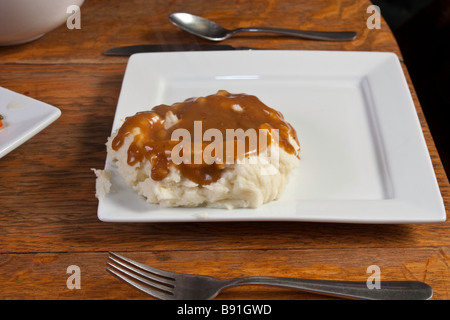 Mashed potatoes and gravy on a white plate - Stock Photo