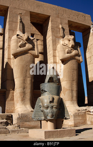 Carved granite head of Ramses ii and osiris pillars, The Ramesseum [Mortuary Temple], 'West Bank', Luxor, Egypt - Stock Photo