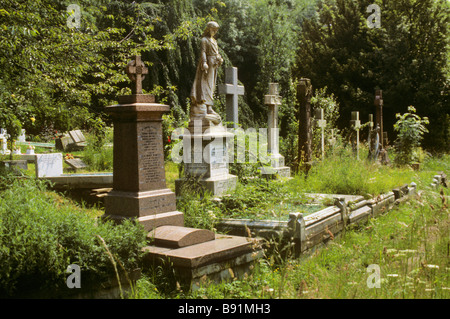 An overgrown row of headstones and grave markers in Highgate Cemetery, London, England. - Stock Photo