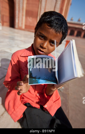 Boy trying to Sell Postcards inside the Friday Mosque in Fatehpur Sikri India - Stock Photo