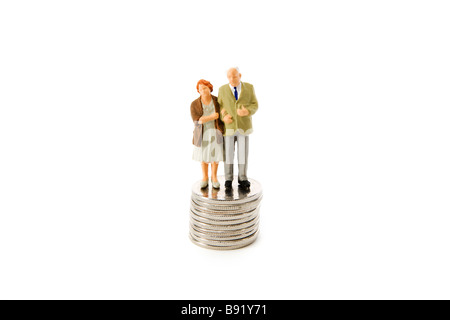 Senior couple standing on pile of coins. - Stock Photo