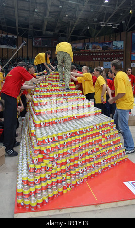 Specially trained Krasnoyarsk students broke a world record and built the largest two meter high canned beef pyramid - Stock Photo