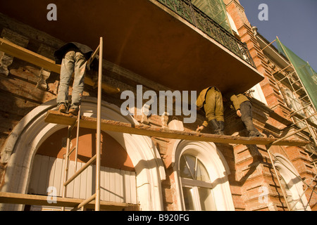 Workmen on scaffolding repairing facade of red brick building, Yekaterinburg, Urals, Russia - Stock Photo