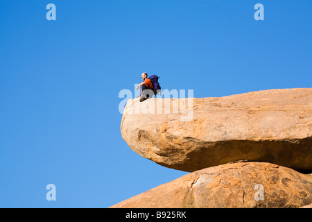 Man sitting on rock staring out at the view bellow, low angle view. Richtersveld National Park, Northern Cape, South - Stock Photo