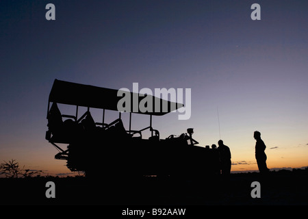 4x4 game viewer and tourists silhouetted at sunset Okavango Delta Botswana - Stock Photo