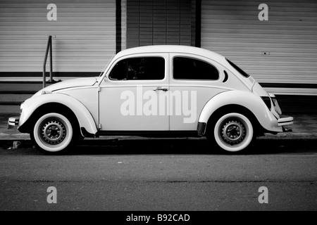 vintage white volkwagen beetle with white side tires parked on the street - Stock Photo