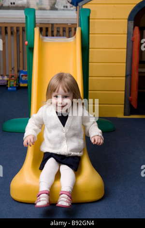 Two Year Old Girl Sliding Down - Stock Photo