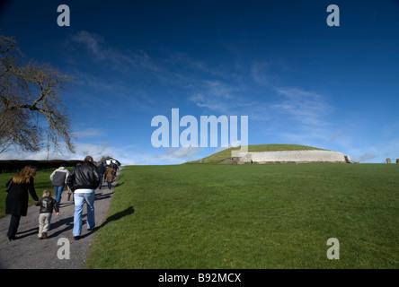 Tourists walking towards Newgrange passage grave County Meath Ireland - Stock Photo