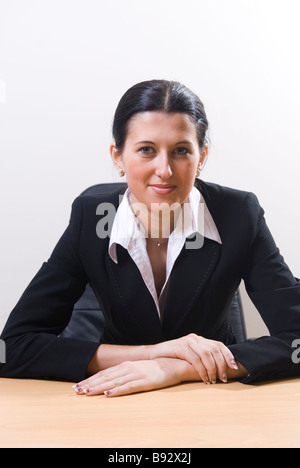 Beautiful business woman wearing a suit sitting in office - Stock Photo