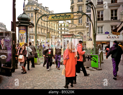 Parisians of different ages and races congregate around the sign for the Cadet metro subway stop - Stock Photo
